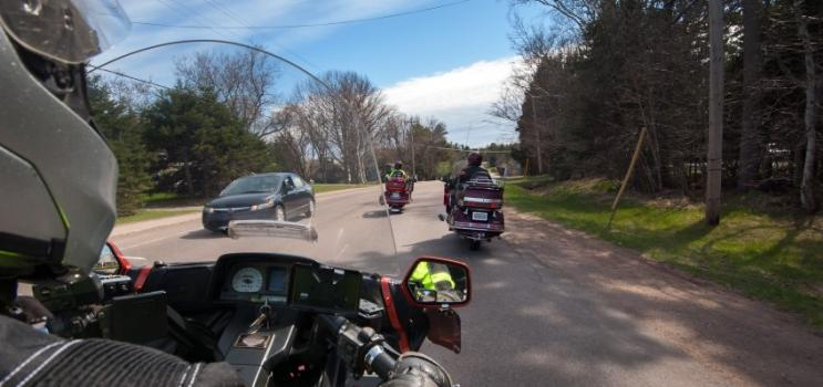Image taken from viewpoint of motorcycle driver on rural PEI road with other motorcycles in front and car in opposing lane