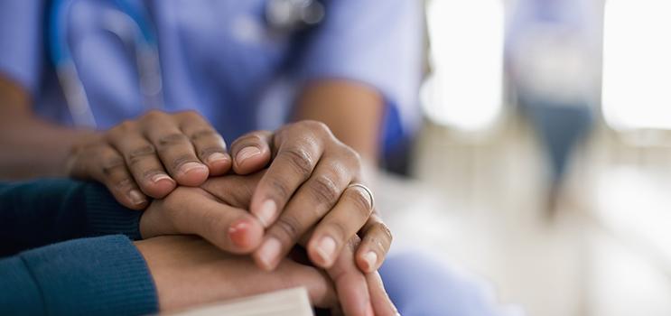 Un professionnel de la santé a les deux mains sur les mains d'une femme pour montrer son confort.