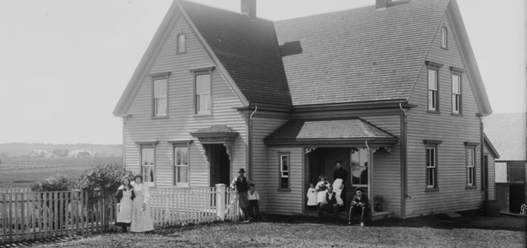 Exterior of the Brehaut house in Alexandra, Prince Edward Island, ca. 1890-1906. The family is posed on the front porch and in front of the fence. Rural landscape in background.