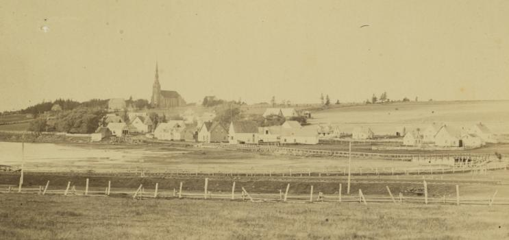 Community of St. Peters, Prince Edward Island, ca. 1870-1880. A wooden bridge across the St. Peters Bay can be seen, as well as a church in the background. Several other buildings and structures are also visible. A small boat is in the lower left corner.