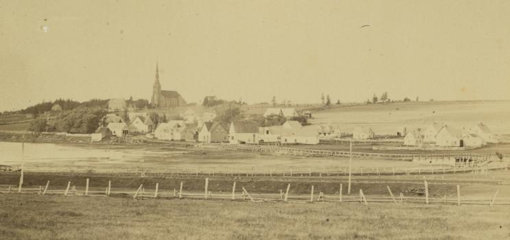 La communauté de St. Peters,à l'Île-du-Prince-Édouard,vers 1870-1880. On peut voir un pont de bois surplombant la baie de St. Peters,une église en arrière-plan,plusieurs bâtiments et structures,ainsi qu'une petite embarcation dans le coin gauche inférieur