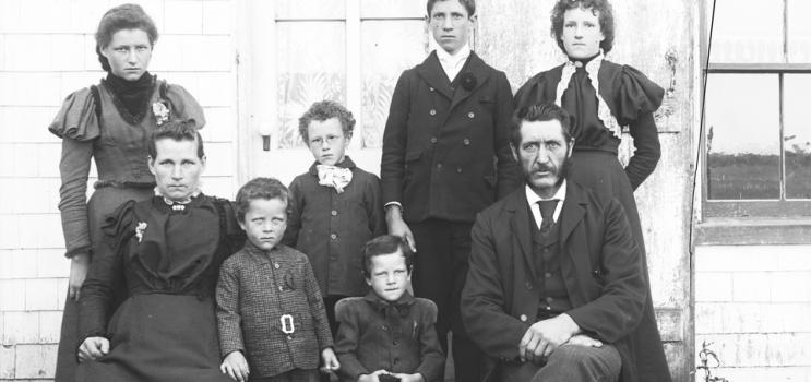 Family consisting of a man, woman, and six children posing for photograph in front of a house