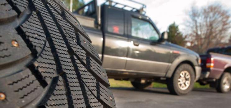Studded tire in foreground and two quarter tonne trucks in background