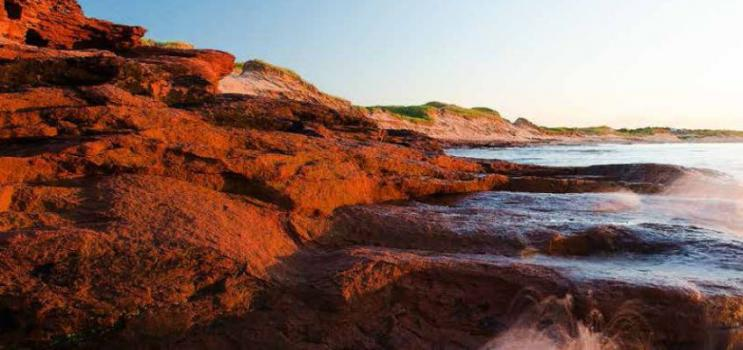 Scenic image of a PEI beach with waves crashing against the red cliffs