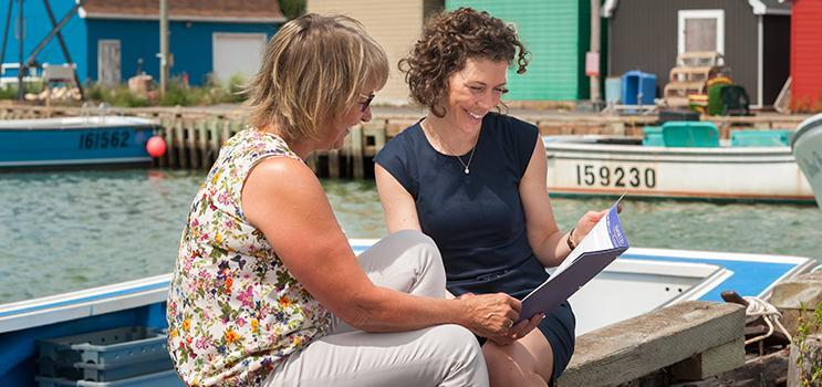 Image of two women sitting on dock at a PEI fishing harbour looking over a brochure