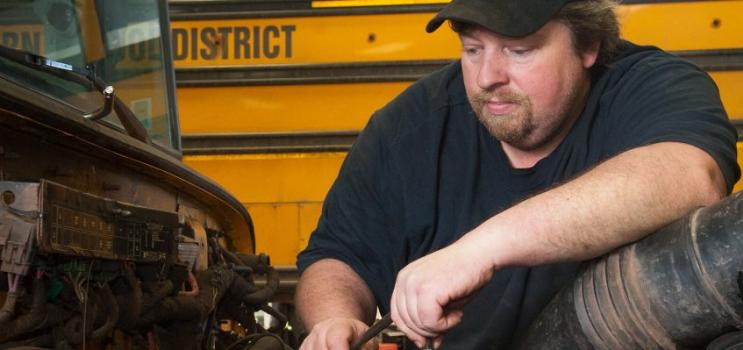 Male heavy duty mechanic working on equipment
