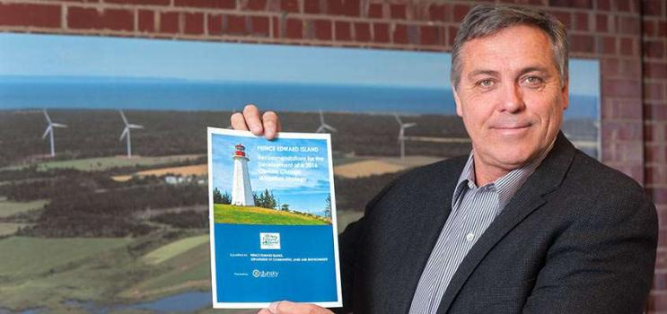 Minister Robert Mitchell holds a copy of the Recommendations for a PEI Climate Change Mitigation Strategy