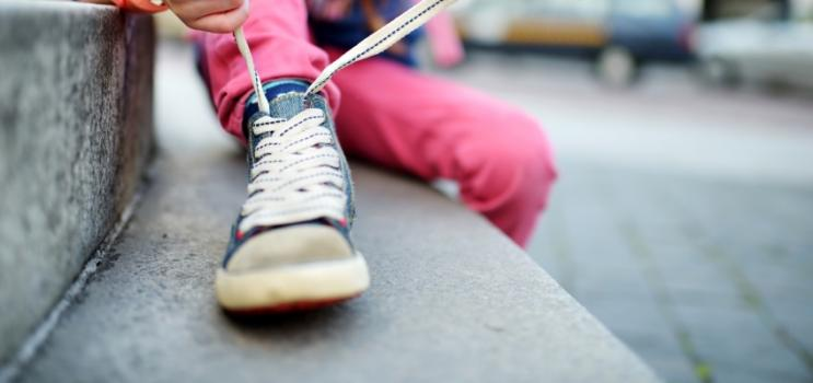 Image of small child tying shoe laces