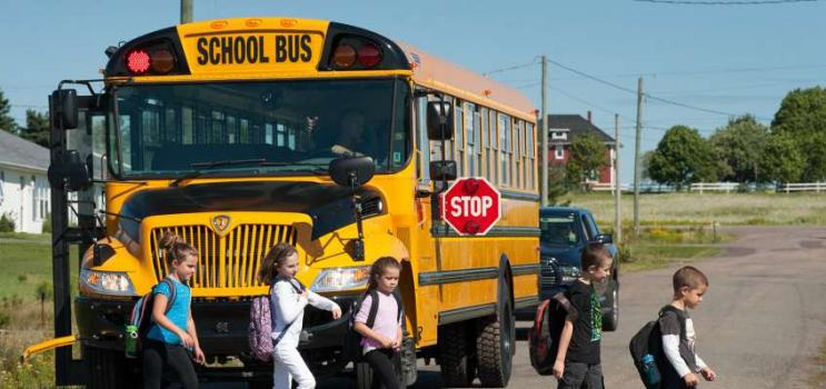 Children exiting a school bus with amber and red lights flashing on PEI country road
