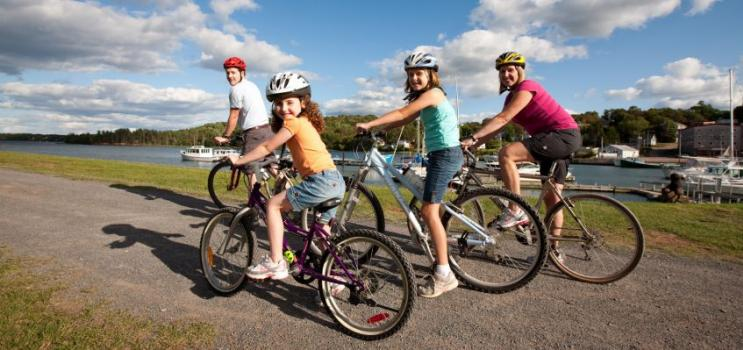 Family of four wear bicycle helmets on Confederation Trail