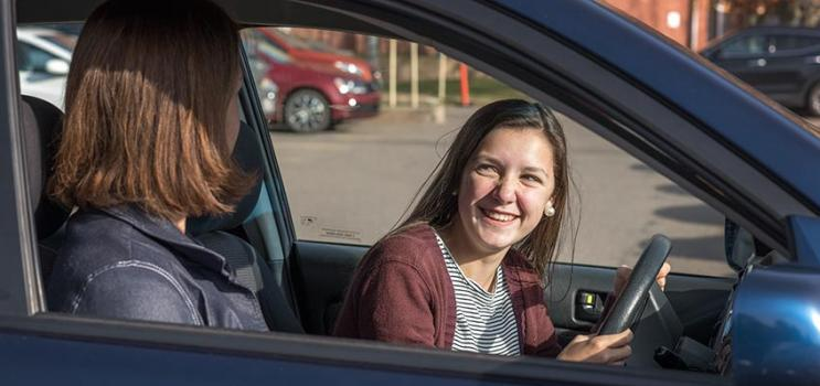 Young driver sits in drivers seat with adult on passenger side