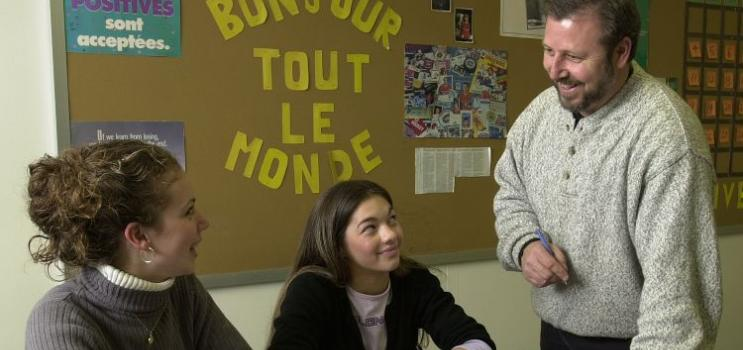 Two female student speak with teacher in French classroom