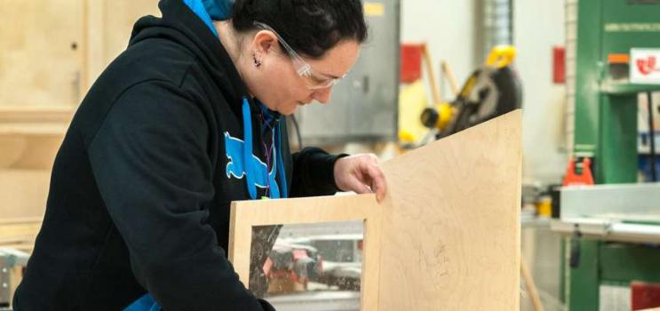 Female working in a woodworking shop on a project