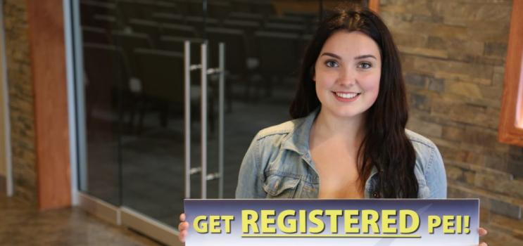 """Young woman holding sign that reads """"Get Registered PEI"""" for PEI plebiscite on electoral reform"""
