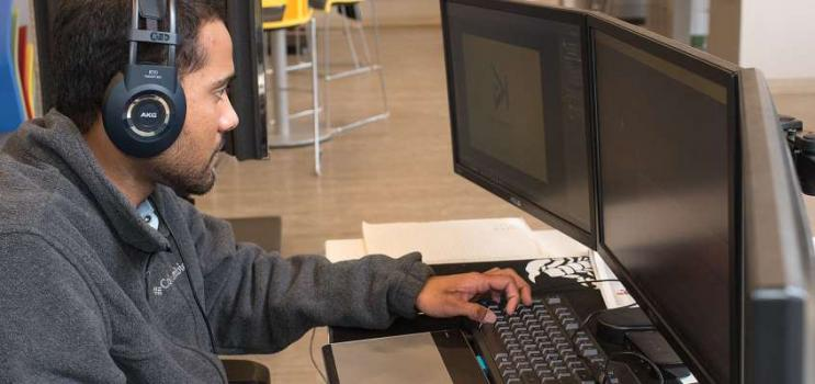 Young male works on computer at Startup Zone, PEI