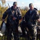 Two men with goose decoys in background. One is holding a dead goose.