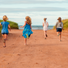 Children running down red dirt road toward a PEI beach