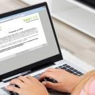 Une femme portant une chemise rose et un jean complétant l'enquête sur l'évaluation des besoins en matière de diabète sur un ordinateur portable