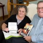 Male and female seniors display books received from home library service