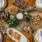Overhead shot of rustic wooden table set with PEI foods and wine
