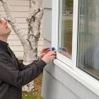 Male home energy inspector takes a reading at a picture window