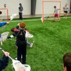 Group of school children learning to play lacrosse