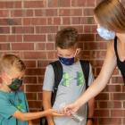 School age children and adult wearing non-medical mask inside a school