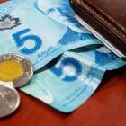 Image of two $50 bill, toonie and quarter next to a wallet