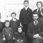 Famille constituée d'un homme, d'une femme et de six enfants prise en photo devant une maison