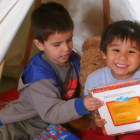 Two children enjoying books from the library.
