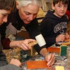 Female demonstrating leather craft to youth