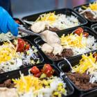 Staff person preparing individual school lunch containers