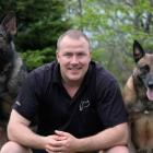 Duke Ferguson kneels with his German Shepherd dog