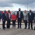 image of eight people standing shoulder to shoulder