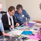 Four people at a table working on scrapbooks