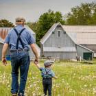 Photo contest winning photo shows farmer and young child walking towards a barn