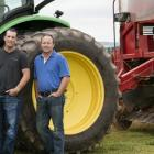 Murphy farm family of China Point stand in front of tractor and potato harvester in field