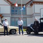 Image of three people standing in front of two antique cars