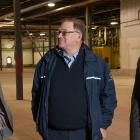 Premier MacLauchlan and Minister MacDonald standing in facility with Ron MacDougall