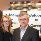 Minister Brown and three other people standing in front of Career Bridges sign and three of them are holding an information brochure.