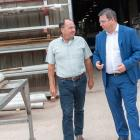 Two men standing inside a fabrication yard work area