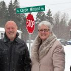 Minister Biggar and thre other people stand in front of the Clyde Minard Way street sign.