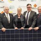 People standing shoulder to shoulder behind a solar panel.