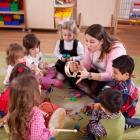 image of a teacher reading to children in a circle