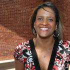 Deborah Langston stands outdoors in front of a red brick building