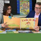 Teacher and Minister of Education sit in a classroom looking a new resource book