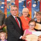 Photo shows Minister Brown surrounded by adults and children holding wooden plaques