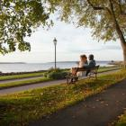A man and a woman sit on a bench overlooking the harbour in Victoria Park in a fall setting.