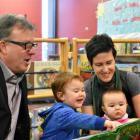 Minister Doug Currie reads a story with Charlie and Rosie and their mother Jinny Greaves.