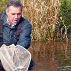 Minister Mitchell releasing fish into a river